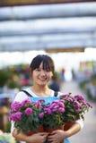 Ευτυχής θηλυκός ασιατικός ανθοκόμος που εξετάζει το χαμόγελο καμερών στοκ φωτογραφία