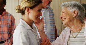 Ευτυχής θηλυκός γιατρός και ανώτερη γυναίκα που φαίνονται πρόσωπο με πρόσωπο 4k φιλμ μικρού μήκους