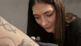 Ευτυχής θηλυκός καλλιτέχνης δερματοστιξιών στο στάδιο της εργασίας, άποψη κινηματογραφήσεων σε πρώτο πλάνο για το πρόσωπο φιλμ μικρού μήκους