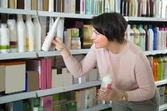 Ευτυχής θηλυκός πελάτης που επιλέγει το εδαφοβελτιωτικό για την τρίχα στην ομορφιά ST Στοκ εικόνα με δικαίωμα ελεύθερης χρήσης