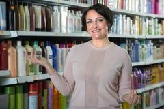 Ευτυχής θηλυκός πελάτης που επιλέγει το εδαφοβελτιωτικό για την τρίχα στην ομορφιά ST Στοκ Εικόνα
