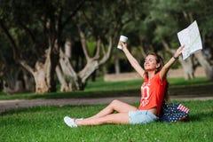 Ευτυχής θηλυκή χαλάρωση τουριστών στο πάρκο στοκ εικόνα με δικαίωμα ελεύθερης χρήσης