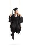 Ευτυχής θηλυκός απόφοιτος φοιτητής σε μια ταλάντευση Στοκ εικόνες με δικαίωμα ελεύθερης χρήσης