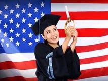 Ευτυχής θηλυκός ασιατικός σπουδαστής με το υπόβαθρο ΑΜΕΡΙΚΑΝΙΚΩΝ σημαιών Στοκ Φωτογραφία
