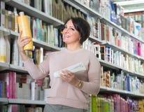 Ευτυχής θηλυκός πελάτης που επιλέγει το εδαφοβελτιωτικό για την τρίχα στην ομορφιά ST Στοκ φωτογραφία με δικαίωμα ελεύθερης χρήσης