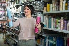 Ευτυχής θηλυκός πελάτης που επιλέγει το εδαφοβελτιωτικό για την τρίχα στην ομορφιά ST Στοκ φωτογραφίες με δικαίωμα ελεύθερης χρήσης