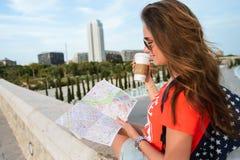 Ευτυχής θηλυκός τουρίστας με έναν χάρτη στην πόλη των τεχνών και των επιστημών στη Βαλένθια στοκ εικόνες