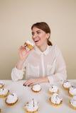 Ευτυχής διασκεδάζοντας νέα γυναίκα που χαμογελά και που τρώει τα κέικ Στοκ εικόνα με δικαίωμα ελεύθερης χρήσης