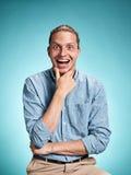 Ευτυχής διεγείρετε το νεαρό άνδρα που χαμογελά πέρα από το μπλε υπόβαθρο στοκ φωτογραφία