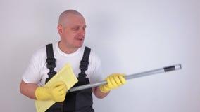 Ευτυχής καθαριστής που χρησιμοποιεί τη σφουγγαρίστρα όπως την κιθάρα απόθεμα βίντεο