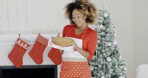 Ευτυχής καθιερώνουσα τη μόδα νέα γυναίκα με ένα επιδόρπιο Χριστουγέννων απόθεμα βίντεο