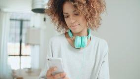 Ευτυχής και εύθυμη νέα γυναίκα που απολαμβάνει τη μουσική και που κρατά το τηλέφωνο φιλμ μικρού μήκους