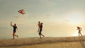 Ευτυχής και ξένοιαστη παιδική ηλικία Παιδιά που παίζουν με τον παλαιότερο ικτίνο, που τρέχει πέρα από την άμμο φιλμ μικρού μήκους