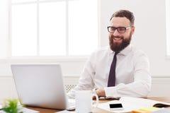 Ευτυχής και χαλαρωμένος επιχειρηματίας με το lap-top στο σύγχρονο άσπρο γραφείο Στοκ Εικόνες