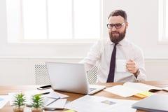 Ευτυχής και χαλαρωμένος επιχειρηματίας με το lap-top στο σύγχρονο άσπρο γραφείο Στοκ Εικόνα