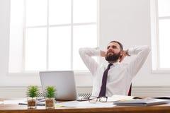 Ευτυχής και χαλαρωμένος επιχειρηματίας με το lap-top στο σύγχρονο άσπρο γραφείο Στοκ εικόνα με δικαίωμα ελεύθερης χρήσης