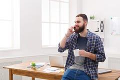 Ευτυχής και χαλαρωμένος κινητός στην αρχή συζήτησης επιχειρηματιών Στοκ Εικόνα