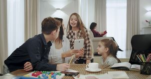 Ευτυχής και χαμογελώντας μητέρα που βοηθά τα παιδιά της σε ένα σχολικό πρόγραμμα αυτοί που χρησιμοποιούν μια ταμπλέτα για να επιλ απόθεμα βίντεο
