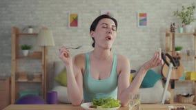 Ευτυχής και χαρούμενη νέα φίλαθλη γυναίκα που τρώει τα λαχανικά που κάθονται στον πίνακα απόθεμα βίντεο