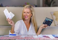 Ευτυχής και όμορφη ξανθή καυκάσια γυναίκα που χαμογελά το χαλαρωμένο εισόδημα χρημάτων υπολογισμού επιτυχές εσωτερικό και το οικο στοκ εικόνες