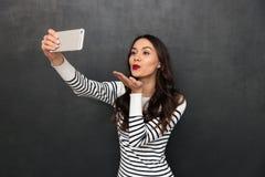 Ευτυχής καλή γυναίκα brunette στο πουλόβερ που κάνει selfie στο smartphone Στοκ εικόνες με δικαίωμα ελεύθερης χρήσης