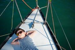 Ευτυχής καπετάνιος παιδάκι που εναπόκειται στην ευχαρίστηση στη βάρκα πολυτέλειάς του στοκ φωτογραφία με δικαίωμα ελεύθερης χρήσης