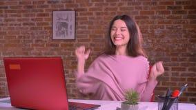 Ευτυχής καυκάσια επιχειρηματίας που χορεύει και που κάνει ευτυχώς τα σημάδια κλαψουρίσματος καθμένος στον πίνακα μπροστά από το l απόθεμα βίντεο