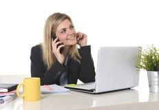 Ευτυχής καυκάσια ξανθή εργασία επιχειρησιακών γυναικών που μιλά στο κινητό τηλέφωνο στο γραφείο υπολογιστών γραφείων Στοκ Εικόνα