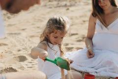Ευτυχής καυκάσια οικογένεια στο άσπρο παιχνίδι φορεμάτων, μητέρων και μπαμπάδων με το μικρό κορίτσι με τα παιχνίδια άμμου που παί στοκ εικόνες