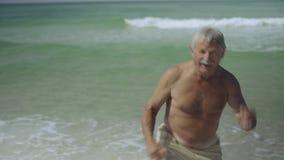 Ευτυχής καυκάσιος αμερικανικός αρσενικός πρεσβύτερος που απολαμβάνει τον υπαίθριο τρόπο ζωής του που χορεύει στην παραλία ΗΠΑ 4k φιλμ μικρού μήκους