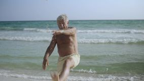 Ευτυχής καυκάσιος αμερικανικός αρσενικός πρεσβύτερος που απολαμβάνει τον υπαίθριο τρόπο ζωής του στην παραλία και που κάνει τις e φιλμ μικρού μήκους
