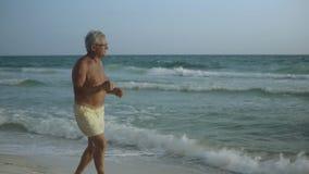 Ευτυχής καυκάσιος αμερικανικός αρσενικός πρεσβύτερος που απολαμβάνει τον υπαίθριο τρόπο ζωής του που χορεύει στην παραλία ΗΠΑ 4k απόθεμα βίντεο
