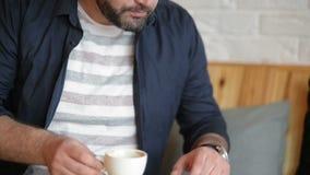 Ευτυχής καυκάσιος επιχειρηματίας στα επίσημα ενδύματα που χαμογελούν και που εξετάζουν την οθόνη smartphone του πίνοντας τον καφέ απόθεμα βίντεο