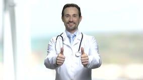 Ευτυχής καυκάσιος χειρούργος που παρουσιάζει δύο αντίχειρες απόθεμα βίντεο