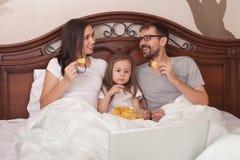 Ευτυχής κινηματογράφος οικογενειακής προσοχής στο κρεβάτι και κατανά στοκ εικόνες