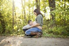 Ευτυχής κοιλιά εκμετάλλευσης παιδιών της εγκύου γυναίκας στο δάσος στοκ εικόνες