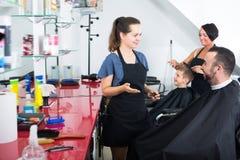Ευτυχής κομμωτής γυναικών που μιλά στο θηλυκό πελάτη Στοκ Φωτογραφίες