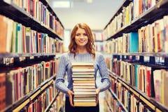 Ευτυχής κορίτσι ή γυναίκα σπουδαστών με τα βιβλία στη βιβλιοθήκη στοκ φωτογραφίες