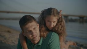Ευτυχής κουβεντιάζοντας οικογένεια που στηρίζεται στη θερινή παραλία απόθεμα βίντεο