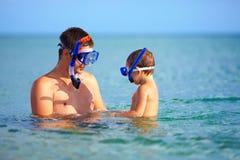 Ευτυχής κολύμβηση με αναπνευστήρα πατέρων και γιων Στοκ Φωτογραφία