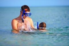 Ευτυχής κολύμβηση με αναπνευστήρα πατέρων και γιων Στοκ φωτογραφία με δικαίωμα ελεύθερης χρήσης