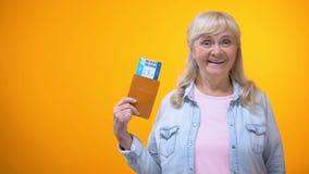 Ευτυχής κυρία συνταξιούχων που παρουσιάζει το διαβατήριο και εισιτήρια, διαφήμιση ταξιδιωτικών γραφείων απόθεμα βίντεο