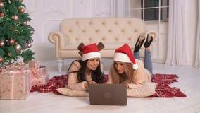 Ευτυχής κυρία δύο με το PC στα επίπεδα Χριστούγεννα απόθεμα βίντεο