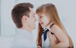 Ευτυχής κόρη εκμετάλλευσης πατέρων στο γέλιο χεριών που γυρίζουν στο πρόσωπό του στοκ εικόνα