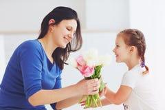 Ευτυχής κόρη που δίνει στη μητέρα μια ανθοδέσμη λουλουδιών άνοιξη Στοκ εικόνες με δικαίωμα ελεύθερης χρήσης