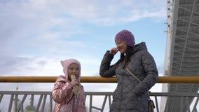 Ευτυχής κόρη που τρώει το χοτ-ντογκ και που μιλά με τη μητέρα στην πόλη το χειμώνα απόθεμα βίντεο