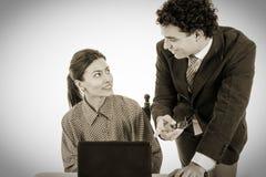 Ευτυχής κύριος και χαμογελώντας γραμματέας που εργάζεται μαζί στο lap-top Στοκ Φωτογραφίες