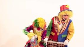 Ευτυχής κλόουν τσίρκων που παρουσιάζει τι έχει στο καλάθι της στον άλλο χαμογελώντας κλόουν απόθεμα βίντεο