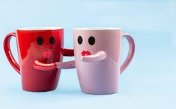 Ευτυχής λέξη Παρασκευών Δύο φλιτζάνια του καφέ σε ένα μπλε υπόβαθρο με ένα χαμόγελο που αντιμετωπίζει την κούπα, που αγκαλιάζει η στοκ φωτογραφίες