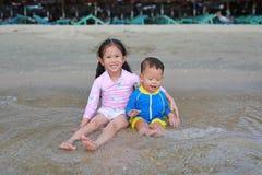 Ευτυχής λίγη ασιατική αδελφή και αυτή λίγος αδελφός κύματα κολύμβησης κοστουμιών συνεδρίασης και παιχνιδιού της θάλασσας στην παρ στοκ φωτογραφίες με δικαίωμα ελεύθερης χρήσης